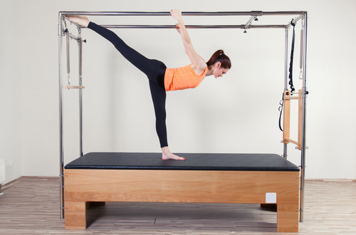 Pilates aerobic instructor woman in trap table fitness exercise.